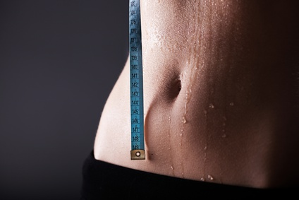 Fitness woman sweaty sporty belly after exercise with measuring tape, weight loss concept